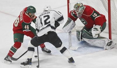 Minnesota Wild's Jared Spurgeon, left, tries to keep Los Angeles Kings' Marian Gaborik of Czech Republic away from the puck as goalie Devan Dubnyk guards the net in an NHL hockey game, Monday, Feb. 27, 2017, in St. Paul, Minn. (AP Photo/Jim Mone)