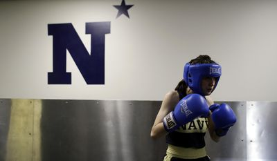 In this Feb. 24, 2017 photo, Midshipman Sophie Lekas of Willowbrook, Ill., warms up in a hallway before her 112-lb boxing match during the U.S. Naval Academy's Brigade Boxing Championships in Annapolis, Md. All Midshipmen are required to participate in boxing as part of their physical education. Participants in the brigade championships are member's of the Academy's boxing club sport team. (AP Photo/Patrick Semansky)