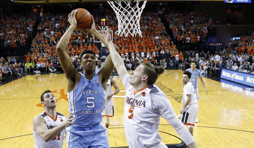 North Carolina forward Tony Bradley (5) takes a shot as Virginia guard Kyle Guy (5) defends during the first half of an NCAA college basketball game in Charlottesville, Va., Monday, Feb. 27, 2017. (AP Photo/Steve Helber)