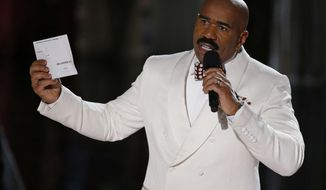 """FILE - In this Dec. 20, 2015, file photo, Steve Harvey holds up the card showing the winners after he incorrectly announced Miss Colombia Ariadna Gutierrez at the winner at the Miss Universe pageant in Las Vegas. After an apparent envelope mix-up led Beatty and co-presenter Faye Dunaway to hand out the Oscars' best picture award to """"La La Land"""" instead of the real winner, """"Moonlight,"""" on Feb. 26, 2017, Harvey tweeted: """"Call me Warren Beatty. I can help you get through this!"""" (AP Photo/John Locher, File)"""