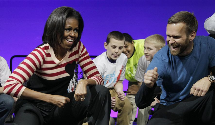 "Then-first lady Michelle Obama and Bob Harper of ""The Biggest Loser,"" right in blue shirt, do the Interlude dance during a ""Let's Move"" event with children from Iowa schools at the Wells Fargo Arena in Des Moines, Iowa, in this Feb. 9, 2012, file photo. Harper tells TMZ he suffered a heart attack and was hospitalized for several days in February 2017. (AP Photo/Carolyn Kaster, File)"