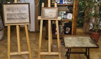 This photo taken Sunday, Feb. 26, 2017 in Krakow, Poland shows an 18-century map of Poland built into a small table and two old drawings that were returned to Poland Sunday by Austria's Horst von Waechter, whose family had looted them from Krakow during World War II. Waechter's father, Otto von Waechter, was a Nazi governor of the occupied city. (Office of the Governor Malopolska via AP)