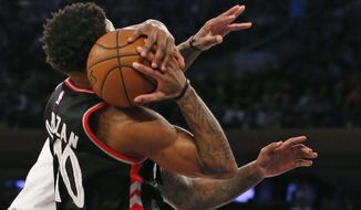 Toronto Raptors guard DeMar DeRozan (10) tries to hold onto the ball after New York Knicks center Kyle O'Quinn, left, (whose hands are visible at right) nearly knocked it from his hands, in the first half of an NBA basketball game at Madison Square Garden in New York, Monday, Feb. 27, 2017. (AP Photo/Kathy Willens)
