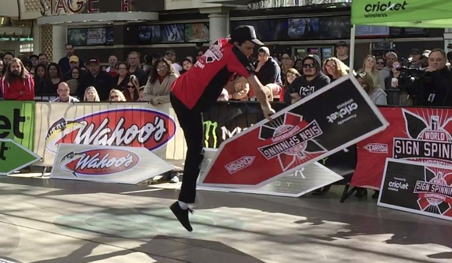 In this photo taken Friday, Feb. 24, 2017, Clint Hartman, a sign spinner from Portland, Ore., performs a routine in downtown Las Vegas during the annual World Sign Spinning Championships. In multiple heats with rap, hip-hop and pop tunes blasting, more than 100 competitors twirled the arrow-shaped sign in front of a cheering crowd. (AP Photo/Regina Garcia Cano)