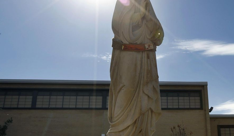 In this photo taken Feb. 22, 2017, Black Hawk Memorial's Shawn Scoles guides the statue of the Virgin Mary honoring the Sullivan brothers in the front of the Columbus High Schoo in Waterloo, Iowa. The five Sullivan siblings died after their ship, the cruiser USS Juneau, was sunk by the Japanese during World War II. (Matthew Putney/The Courier via AP)