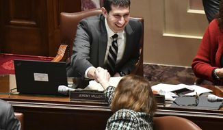 Senator Jeremy Miller,R-Winona, chief author of the Sunday liquor bill, is congratulated by other Senators, Monday, Feb. 27, 2017, in St. Paul, Minn. The Minnesota Legislature has voted to repeal the state's long-standing ban on Sunday liquor sales. The state Senate passed a bill undoing the Prohibition-era ban on a 38-28 vote Monday.   (Glen Stubbe/Star Tribune via AP)