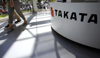 In this May 4, 2016, file photo, visitors walk by a Takata Corp. desk at an automaker's showroom in Tokyo. Japanese auto parts maker Takata Corp. is expected to plead guilty in U.S. District Court in Detroit on Monday, Feb. 27, 2017, to a criminal charge and agree to a $1 billion penalty for concealing a deadly air bag inflator problem. (AP Photo/Shizuo Kambayashi, File)
