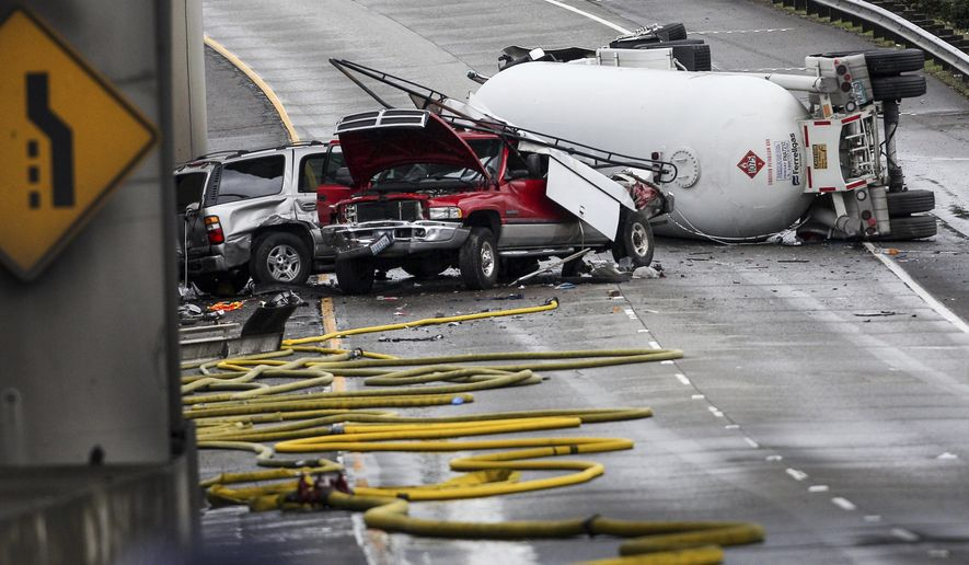 A tanker truck carrying butane lays overturned Monday, Feb. 27, 2017, in Seattle. The semi-truck rolled on a southbound lane that feeds into Interstate 5  on Monday. (Grant Hindsley/seattlepi.com via AP)