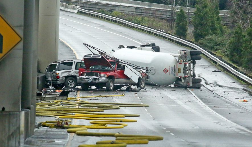 A tanker truck carrying butane lays overturned Monday, Feb. 27, 2017, in Seattle. The Seattle Times reports that the semi-truck rolled on a southbound lane that feeds into Interstate 5 just after 10 a.m. Monday. (Greg Gilbert/The Seattle Times via AP)