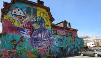 This Feb. 17, 2017 photo shows a colorful mural in the Hill District of Pittsburgh honoring playwright August Wilson and his work. The Hill District offers a rich map of places and stories connected to Wilson's plays, nine of which are set in Pittsburgh. Artist Kyle Holbrook created the mural with children from a local arts program. (AP Photo/Beth J. Harpaz)