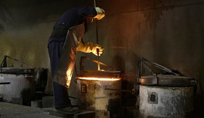 "David Silva, shop foreman at the Pease & Curren foundry, stirs the melting gold class rings of deceased West Point graduates Monday, Feb. 27, 2017, in Warwick, R.I. Forty-one gold class rings were donated this year, most by families in memory of a deceased member of the United States Military Academy at West Point, to be melted into a gold bar for the crafting of the 2018 class rings of graduating members of the ""Long Grey Line,"" (AP Photo/Stephan Savoia)"