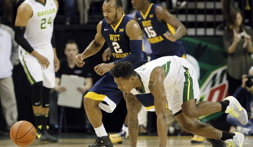West Virginia's Jevon Carter (2) and Baylor's Wendell Mitchell, bottom, chase after a loose ball int he first half of an NCAA college basketball game, Monday, Feb. 27, 2017, in Waco, Texas. (AP Photo/Tony Gutierrez)