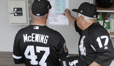 Chicago White Sox manager Rick Renteria looks over his line up with Joe McEwing before a spring training baseball game against the Chicago Cubs Monday, Feb. 27, 2017, in Mesa, Ariz. (AP Photo/Morry Gash)
