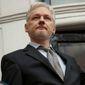 WikiLeaks founder Julian Assange holds a U.N. report as he speaks on the balcony of the Ecuadorean Embassy in London on Feb. 5, 2016. (Associated Press) ** FILE **