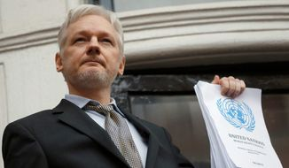 WikiLeaks founder Julian Assange holds a U.N. report as he speaks on the balcony of the Ecuadorean Embassy in London on Feb. 5, 2016. (Associated Press) ** FILE **