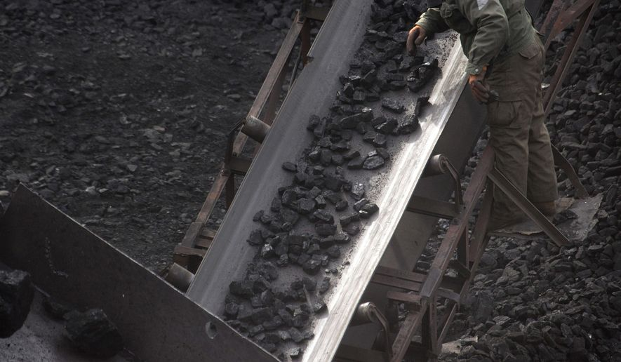 FILE - In this Nov. 4, 2015 file photo, a worker monitors coal being carried along conveyor ramps at a coal mine near Ordos in northern China's Inner Mongolia Autonomous Region. According to official data released Tuesday, Feb. 28, 2017, China's consumption of coal fell in 2016 for a third year in a row as the world's top polluter has emerged as a leader in efforts to tackle climate change. (AP Photo/Mark Schiefelbein, File)