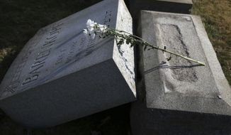 Flowers rest on a damaged headstone at Mount Carmel Cemetery Feb. 28, 2017 in Philadelphia. Scores of volunteers are expected to help in an organized effort to clean up and restore the Jewish cemetery where vandals damaged hundreds of headstones. (AP Photo/Jacqueline Larma)