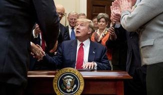 President Donald Trump shakes hands after signing the Waters of the United States (WOTUS) executive order, Tuesday, Feb. 28, 2017, in the Roosevelt Room in the White House in Washington, which directs the Environmental Protection Agency to withdraw the Waters of the United States (WOTUS) rule, which expands the number of waterways that are federally protected under the Clean Water Act. (AP Photo/Andrew Harnik) **FILE**