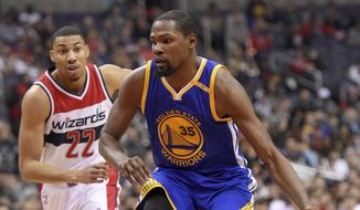 Golden State Warriors forward Kevin Durant (35) dribbles the ball past Washington Wizards forward Otto Porter Jr. (22) during the first half of an NBA basketball game, Tuesday, Feb. 28, 2017, in Washington. (AP Photo/Nick Wass)