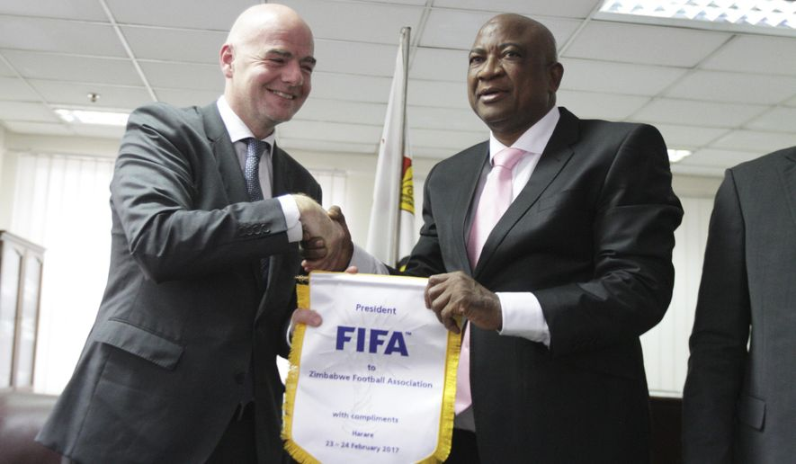 In this image taken  Friday, Feb 24, 2017 Zimbabwe Football Association President Philip Chiyangwa, right, shakes hands with FIFA President Gianni Infantino at a ceremony in Harare, Zimbabwe .  Chiyangwa the man driving the campaign to unseat longtime African soccer boss Issa Hayatou is a multi millionaire Zimbabwean property mogul who dabbles in politics and was once accused of been a spy and put in jail. (AP Photo)