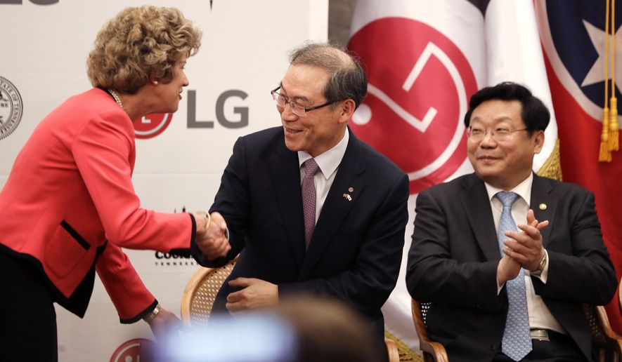 Clarksville, Tenn. Mayor Kim McMillan, left, shakes hands with Dan Song, the president of LG's home appliances division, during an announcement Tuesday, Feb. 28, 2017, in Nashville, Tenn. It was announced that South Korean appliance maker LG Electronics Inc. has selected Clarksville as the site for its washing machine plant in the United States. The 829,000-square-foot facility is projected to cost $250 million and create 600 new jobs. At right is Trade, Industry and Energy Minister Joo Hyung-hwan. (AP Photo/Mark Humphrey)