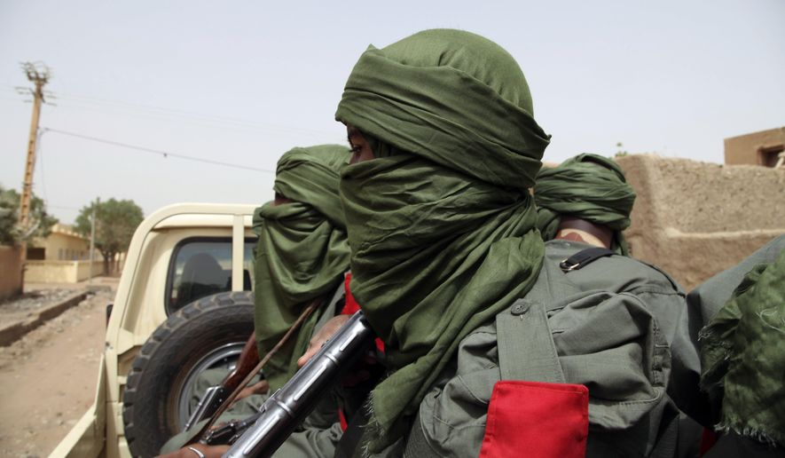 In this photo taken on Thursday, Feb. 23, 2017, Malian troops join with former rebels during a joint patrol in Gao, Mali. Malian soldiers and former Tuareg rebels have staged their first joint patrol in northern Mali, a key step in a 2015 peace agreement meant to help calm a region under threat from multiple extremist and other armed groups. As helicopters with the U.N. peacekeeping mission hovered overhead last week, 50 men in distinctive blue turbans started to patrol the city of Gao, a target of attacks by Islamic extremists including one in January that killed 54. (AP Photo/Baba Ahmed)