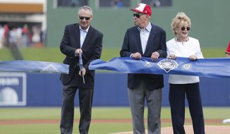 Major League Baseball commissioner Rob Manfred, left, cuts a ribbon to open The Ballpark of the Palm Beaches as Washington Nationals owner Ted Lerner and his wife Annette look on before a spring training baseball game Tuesday, Feb. 28, 2017 in West Palm Beach, Fla. The stadium will serve as the spring training home for both the Washington Nationals and Houston Astros. (AP Photo/John Bazemore)