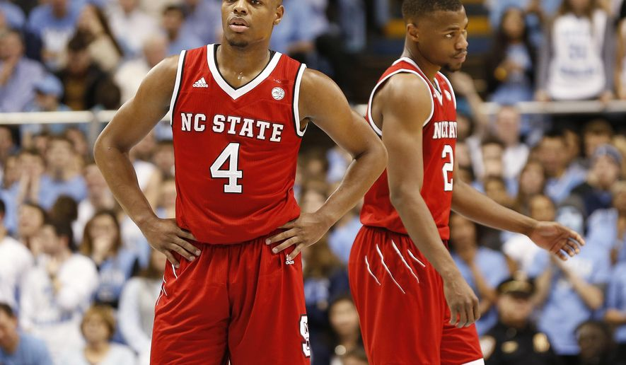 FILE - In this Jan. 8, 2017, file photo, North Carolina State guards Dennis Smith Jr. (4) and Torin Dorn react during the second half of an NCAA college basketball game against North Carolina, in Chapel Hill, N.C. This wasn't what Dennis Smith Jr. envisioned for his freshman _ and possibly only _ season at North Carolina State. Entering the Wolfpack's regular-season finale at Clemson, Smith has been a brilliant individual talent but his team struggled so badly that it ultimately cost coach Mark Gottfried his job. (AP Photo/Ellen Ozier, File)