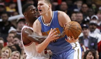 Chicago Bulls' Bobby Portis, left, knocks the ball out of the hands of Denver Nuggets' Nikola Jokic during the second half of an NBA basketball game Tuesday, Feb. 28, 2017, in Chicago. The Nuggets won 125-107. (AP Photo/Charles Rex Arbogast)