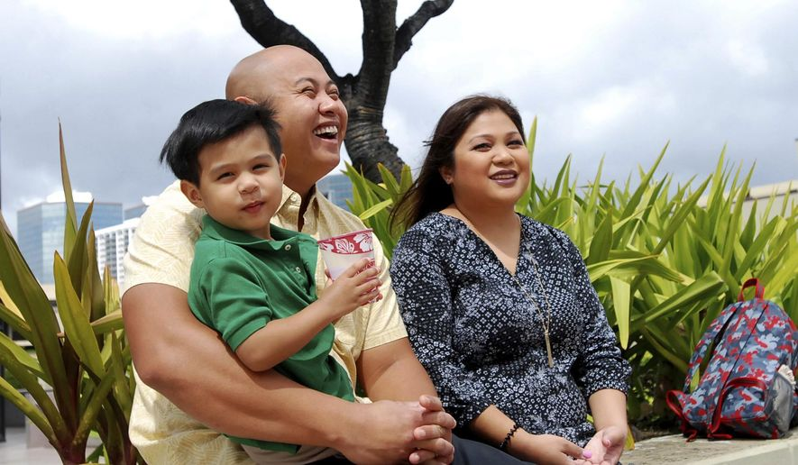 In this Feb. 24, 2017 photo, Peyton Valiente, 3, sits with his parents Rey and Chelsea Valiente as they speak to The Associated Press in Honolulu. Honolulu Police Department Acting Chief Cary Okimoto recently expressed concerns about the handling of a case from two years ago that involved the child, who was severely injured in a day care run by a police officer's wife. Chelsea Valiente says her then-17-month-old son was fine when she dropped him off at the home day care in January 2015. But she received a call from the baby-sitter hours later saying the child was having trouble waking up.  (AP Photo/Caleb Jones)