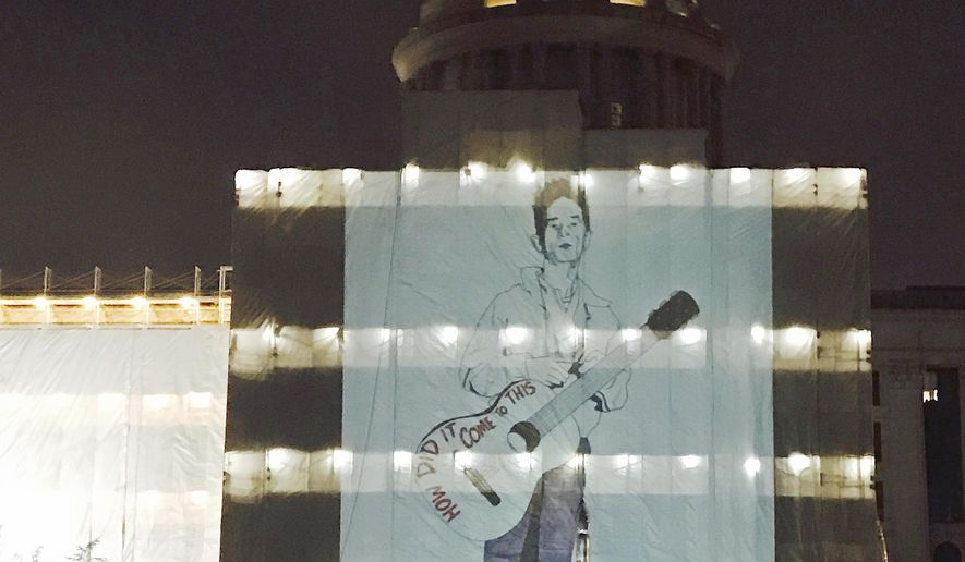 "In this Feb 27, 2017 photo provided by Heide Brandes, an image of folks singer Woody Guthrie is projected on tarps at the Oklahoma Capitol in Oklahoma City. Oklahoma City artist Jack Fowler says he projected an image the iconic singer in an effort to get people to ""shake up the powers that be."" The Oklahoma Office of Management and Enterprise Services said in a statement that the projection is prohibited due to safety concerns for crews working at night on a restoration project at the Capitol. (Heide Brandes via AP)"