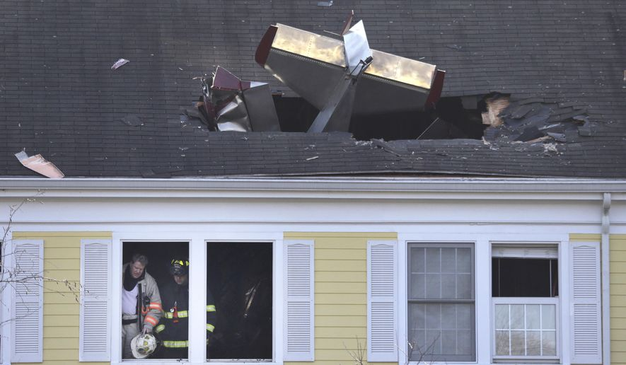 Firefighters investigate the scene after a small plane crashed into the roof of a condominium building across the Merrimack River from Lawrence Municipal Airport, Tuesday, Feb. 28, 2017, in Methuen, Mass.  (AP Photo/Elise Amendola)