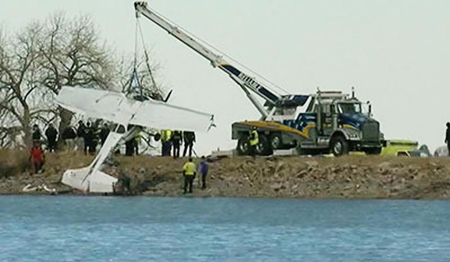 In this image from video provided by KMGH, a small plane is pulled out of water after it crashed into Culver Reservoir near Berthoud, north of Denver on Monday, Feb. 27, 2017. Two men are dead after their small plane crashed into the reservoir in northern Colorado. (KMGH/TheDenverChannel.com via AP)