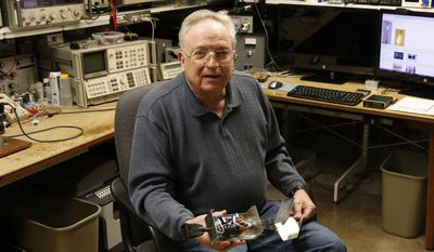 In this Feb. 21, 2017 photo, lifelong ham radio operator and expert tinkerer Tom Thompson, holds a radio wave filter he invented, inside his basement home office, where he operates a ham radio and other devices, in Boulder, Colo. After discovering that radio interference was being caused by high-powered lights from home marijuana growers, Thompson built an electronic filter and has given them to nearby growers. (AP Photo/Brennan Linsley)