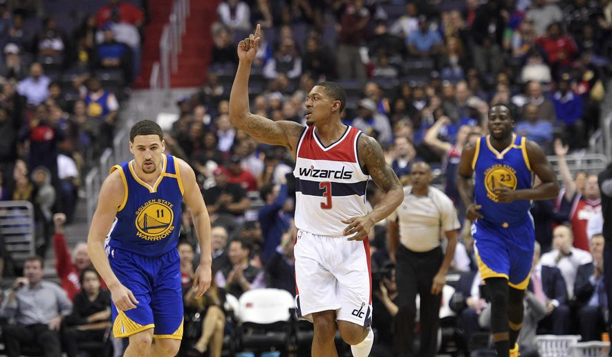 Washington Wizards guard Bradley Beal (3) gestures during the first half of an NBA basketball game next to Golden State Warriors guard Klay Thompson (11) and forward Draymond Green (23), Tuesday, Feb. 28, 2017, in Washington. (AP Photo/Nick Wass)