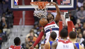 Washington Wizards guard John Wall (2) dunks against the Golden State Warriors during the first half of an NBA basketball game, Tuesday, Feb. 28, 2017, in Washington. (AP Photo/Nick Wass)