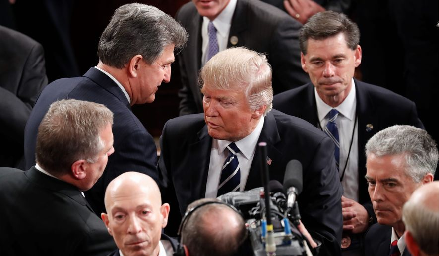Sen. Joe Manchin III, West Virginia Democrat, made a point to congratulate President Trump after his speech to Congress on Tuesday. A political scientist says he is sure to use the footage to campaign next year in the most pro-Trump state in the nation. (Associated Press)
