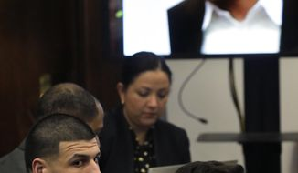 Former New England Patriots tight end Aaron Hernandez, left, sits in court as an image of shooting victim Daniel de Abreu is projected, top right, during his double murder trial at Suffolk Superior Court Wednesday, March 1, 2017, in Boston. Hernandez is charged in the July 2012 killings of Daniel de Abreu and Safiro Furtado who he encountered in a Boston nightclub. The former NFL football player already is serving a life sentence in the 2013 killing of semi-professional football player Odin Lloyd. (AP Photo/Steven Senne, Pool)