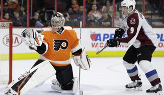 Philadelphia Flyers' Steve Mason, left, catches a shot as Colorado Avalanche's Matt Duchene looks for the rebound during the third period of an NHL hockey game, Tuesday, Feb. 28, 2017, in Philadelphia. Philadelphia won 4-0. (AP Photo/Matt Slocum)