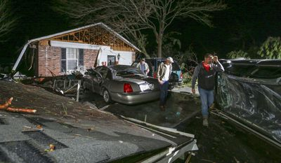 CORRECTS CREDIT TO THE ARKANSAS DEMOCRAT-GAZETTE FROM THE NORTHWEST ARKANSAS DEMOCRAT-GAZETTE - In this Tuesday, Feb. 28, 2017 photo, family members walk between an overturned car, right, and a detached roof, left, at a home along Holiday Terrace in Higginson, Ark., after a storm passed through the White County town. (Stephen B. Thornton/The Arkansas Democrat-Gazette via AP)