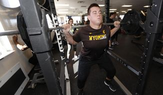 In this Thursday, Feb. 16, 2017, photograph, Wyoming offensive lineman Chase Roullier lifts weights as part of his preparations to take part in the NFL combine, at a workout facility in Centennial, Colo. The 330 college players arriving at the NFL's annual combine have been readying for months to perform for the agents gathered in Indianapolis. (AP Photo/David Zalubowski)