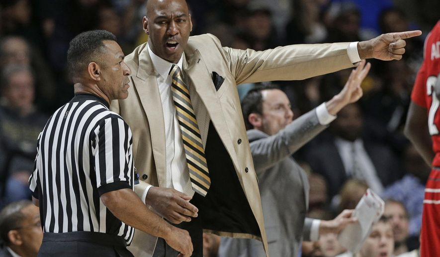 Wake Forest coach Danny Manning, right, argues a call with an official during the first half of the team's NCAA college basketball game against Louisville in Winston-Salem, N.C., Wednesday, March 1, 2017. (AP Photo/Chuck Burton)