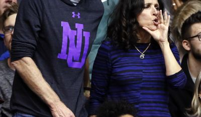 Actress Julia Louis-Dreyfus, right, and her husband Brad Hall react to a call as they watch an NCAA college basketball game between Northwestern and Michigan during the second half Wednesday, March 1, 2017, in Evanston, Ill. Northwestern won 67-65. Brad Hall and Julia Louis-Dreyfus' son Charlie Hall plays at Northwestern basketball team. (AP Photo/Nam Y. Huh)