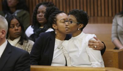 Faith Green, right, is comforted after giving her victim impact speech during the sentencing of ex-husband Gregory Green at Wayne County Circuit Court in Detroit on Wednesday March 1, 2017, for murdering her four children. Green was sentenced to at least 47 years in prison Wednesday for the attack, that also nearly killed Faith Green. (Ryan Garza/Detroit Free Press via AP)