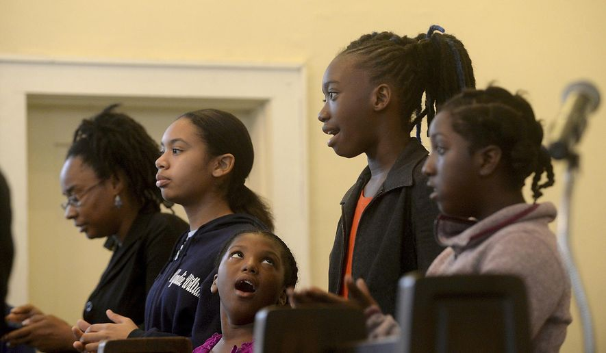 ADVANCE FOR SUNDAY, MARCH 5 AND THEREAFTER - In a Feb. 19, 2017 photo, the youth choir sings during Sunday morning services at Mount Zion Missionary Baptist Church in Orange, Texas. In honor of Black History Month, part of Rev. C.W. Crawford's message to the congregation was on the role the church has played within the community as the first established Black church in Orange, and the part it continues to play in bettering the lives of those within the community. (Kim Brent/The Beaumont Enterprise via AP)