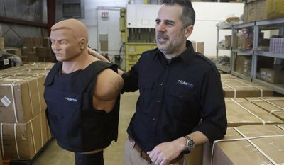 In this Monday, Feb. 27, 2017, photo, Tom Nardone, owner of PriveCo, which sells bulletproof vests, poses in his warehouse in Troy, Mich., with a mannequin wearing a test vest. In more than a hundred videos he's posted on YouTube, Nardone takes aim at racks of ribs, laptop computers and tires to illustrate what a bulletproof vest can do. While he advertised in magazines and went to gun shows, he realized that to reach a wider audience he needed to be online. And he didn't want a demonstration of just the vests. (AP Photo/Carlos Osorio)