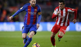 FC Barcelona's Lionel Messi, left, duels for the ball against Sporting Gijon's Carlos Castro during the Spanish La Liga soccer match between FC Barcelona and Sporting Gijon at the Camp Nou stadium in Barcelona, Spain, Wednesday, March 1, 2017. (AP Photo/Manu Fernandez)