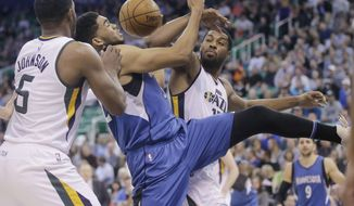 Minnesota Timberwolves center Karl-Anthony Towns, center, battles for a rebound against Utah Jazz's Joe Johnson (6) and Derrick Favors (15) during the first half in an NBA basketball game Wednesday, March 1, 2017, in Salt Lake City. (AP Photo/Rick Bowmer)