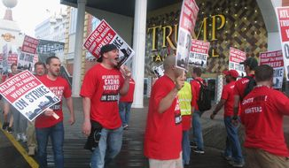 This July 1, 2016, photo shows striking union members on the picket line shortly after a strike began against the Trump Taj Mahal casino in Atlantic City, N.J. On Wednesday, March 1, 2017, owner Carl Icahn reached a deal to sell the casino, which shut down on Oct. 10, 2016, to Hard Rock International and two New Jersey investors. The sale price was not divulged. (AP Photo/Wayne Parry)
