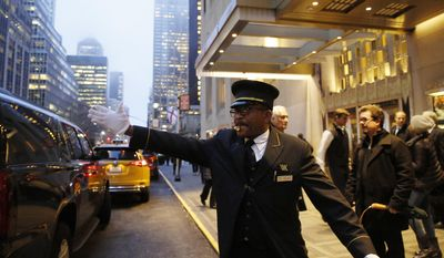 "Veteran doorman Thales Cadet, who claims, ""the world comes to me everyday,"" hails a cab in front of the Waldorf Astoria hotel, Tuesday, Feb. 28, 2017, in New York. Cadet has worked at the hotel for 12 years since coming from his former job at the Plaza Hotel. The hotel, purchased by the Anbang Insurance Group, a Chinese company, is closing Wednesday for two to three years for renovation. (AP Photo/Kathy Willens)"